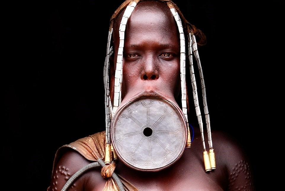 Khi một thành viên nữ của bộ tộc tới tuổi trưởng thành, cô sẽ phải nhổ bỏ hai răng cửa ở hàm dưới, trước khi cắt một lỗ nhỏ ở môi dưới. Một chiếc đĩa gốm nhỏ được lồng vào lỗ này. Kích cỡ đĩa tăng dần, kéo dãn vành môi ra.