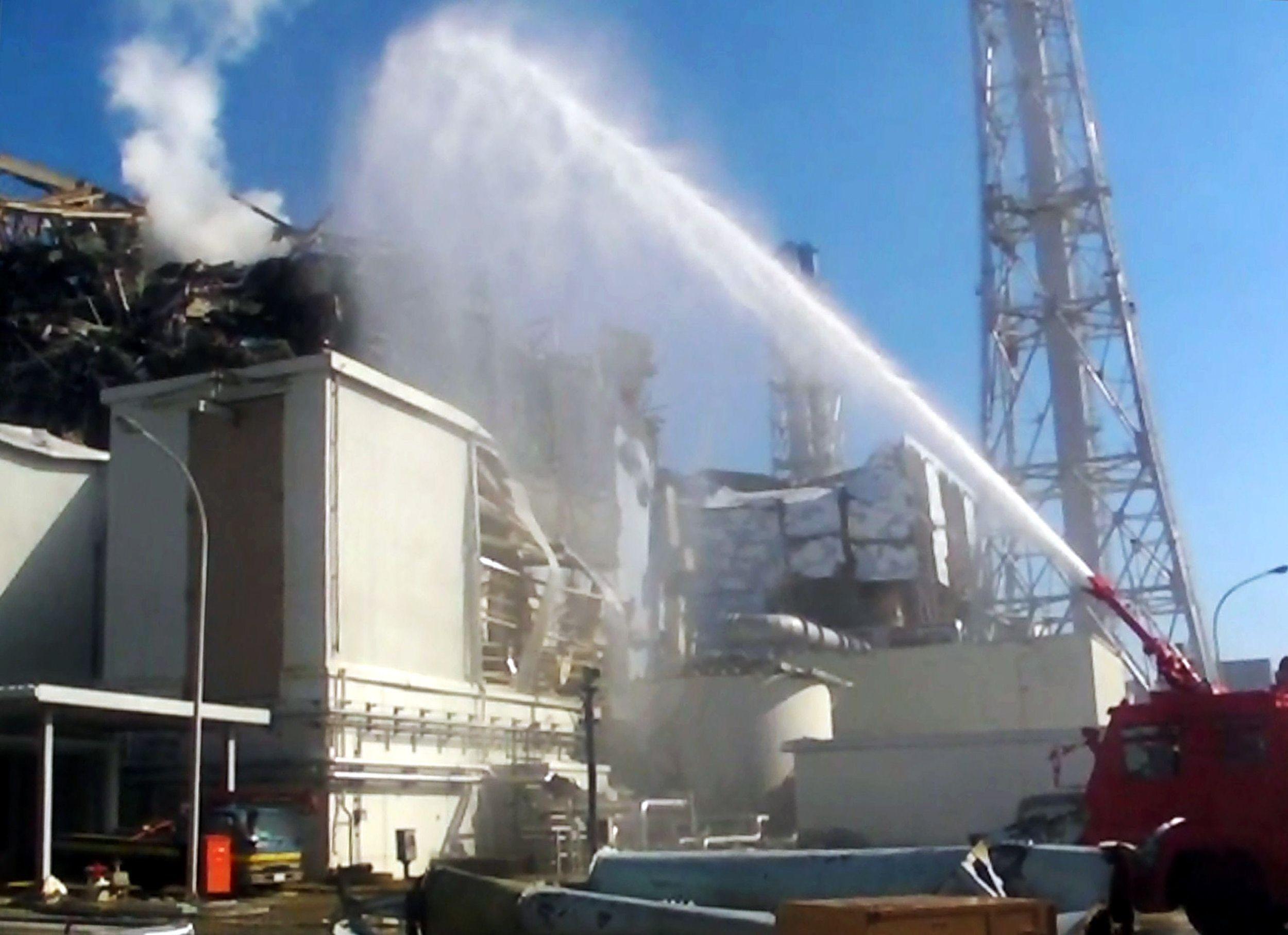 Công nhân phun nước làm mát lò phản ứng uranium ở nhà máy điện hạt nhân Fukushima. Thảm họa sóng thần khiến các lò phản ứng bị hư hại, gây nên thảm họa hạt nhân nghiêm trọng nhất ở Nhật Bản trong thời hiện đại. Ảnh: AFP