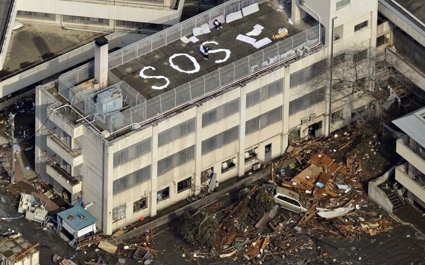 Người dân tạo tín hiệu S.O.S trên nóc một tòa nhà tại thành phố Kesennuma để kêu gọi sự chú ý của lực lượng cứu hộ. Nhiều người chạy lên các tòa nhà cao tầng để trốn ngọn sóng dữ ập vào đất liền ngày 11/3. Ảnh: Reuters