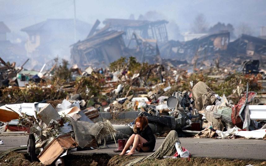 Một cô gái bật khóc giữa khung cảnh hoang tàn sau trận thiên tai ở thành phố Natori, tỉnh Miyagi. Ảnh: EPA