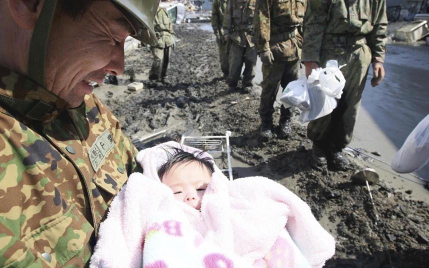 Một thành viên Lực lượng tự vệ Nhật Bản bế một em bé 4 tháng tuổi may mắn sống sót sau trận sóng thần ở thành phố Ishimaki, tỉnh Miyagi. Ảnh: Reuters
