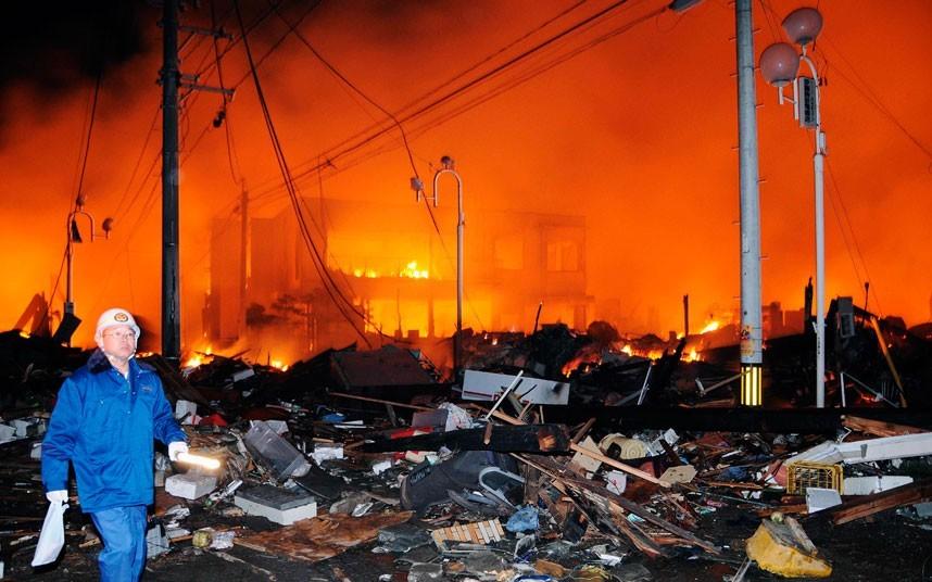 Một nhân viên cứu hộ đi giữa khung cảnh hoang tàn tại thành phố Iwaki, tỉnh Fukushima, vốn là một trong những vùng chịu ảnh hưởng nặng nề nhất. Ảnh: AP