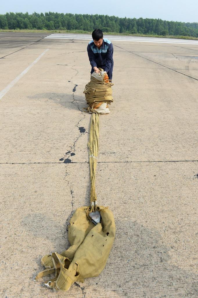 Lính không quân xếp dù lại sau khi máy bay ngắt dù giảm tốc.